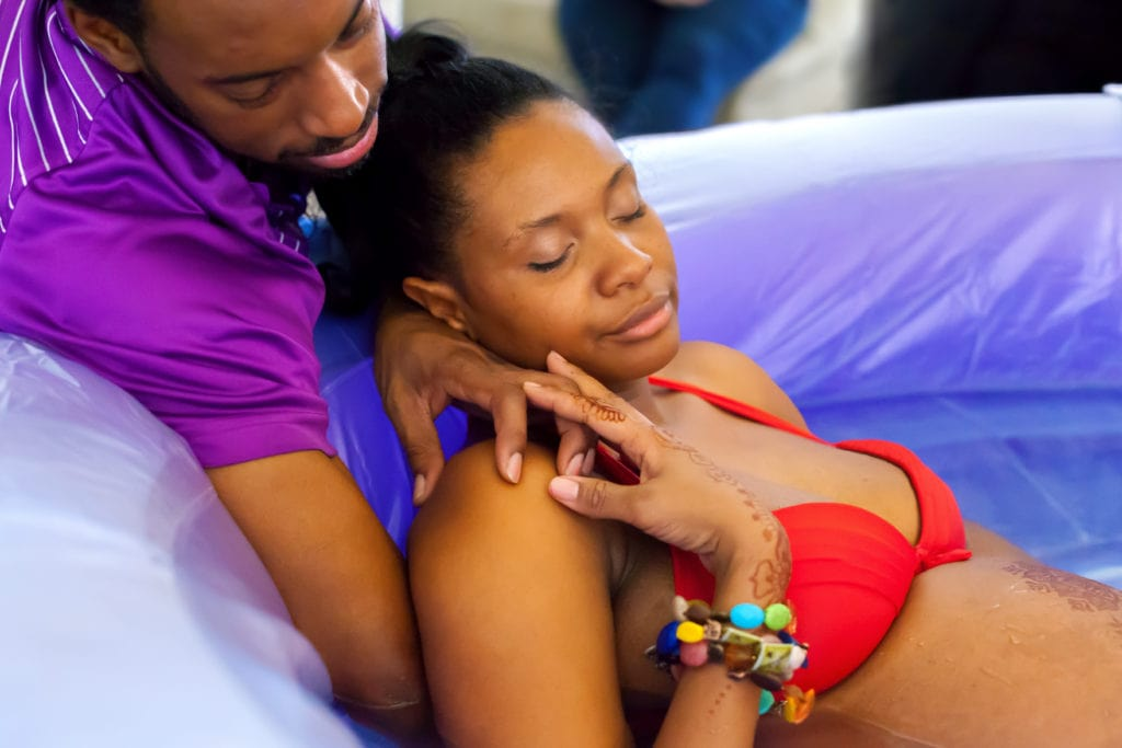 A beautiful African American woman labors peacefully in a birthing tub as her husband comforts her by holding her hand and rubbing her back.